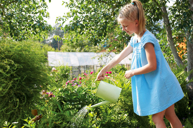 Little girl watering the flowers in the family garden at a summer day, very rural scene stock photography