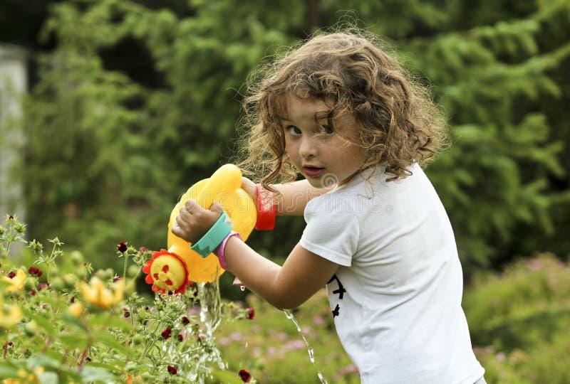 Little girl is watering the flowers in the garden