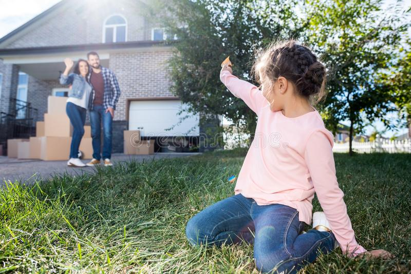 little girl waving to parents while sitting on grass of stock photo