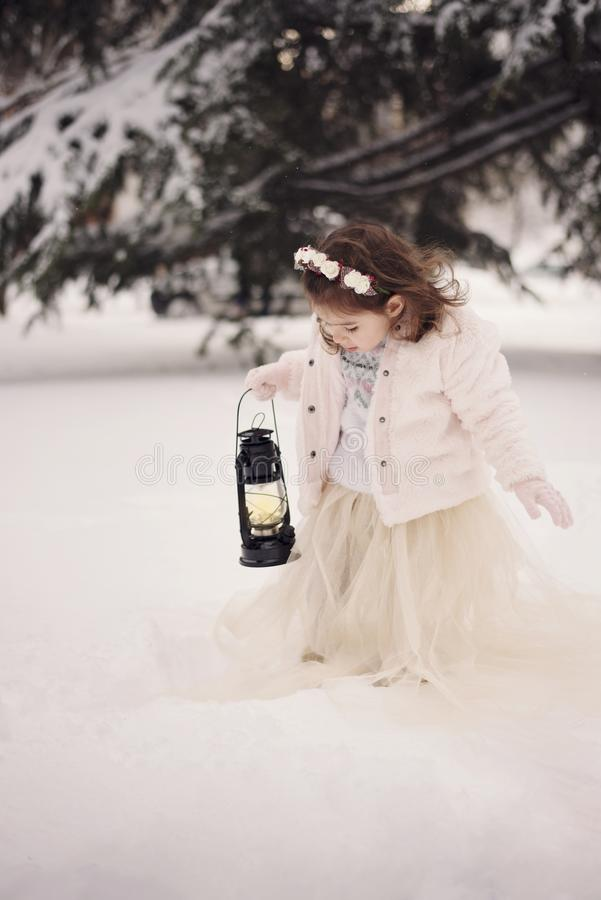 Little girl wearing a beige coat and long dress, looking at lamp with candle standing among the branches, covered with snow in the royalty free stock photos