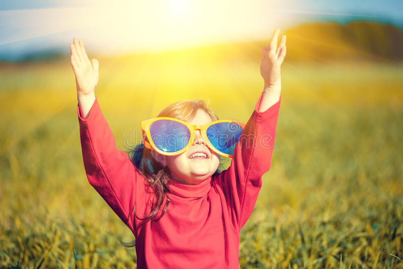 Little girl wearing big sunglasses looking at the sun royalty free stock photography