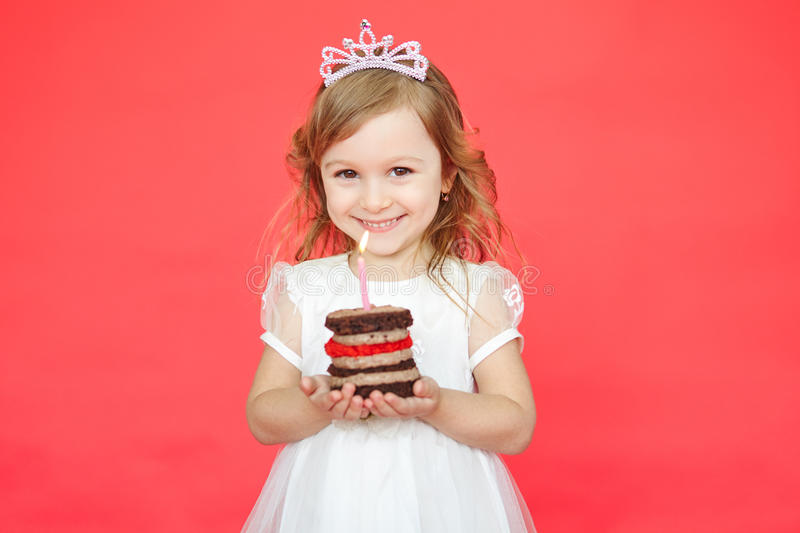 Little girl wearing crown holding a birthday cake. With candle isolated on red background stock photos