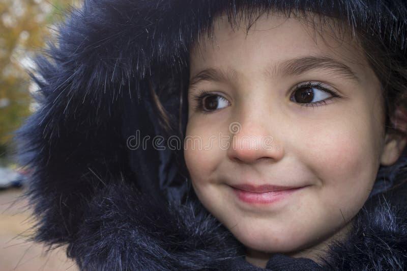 Little girl wearing dark blue winter coat with faux fur hood stock photos