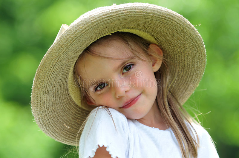 Little girl wearing a hat outdoors royalty free stock photo