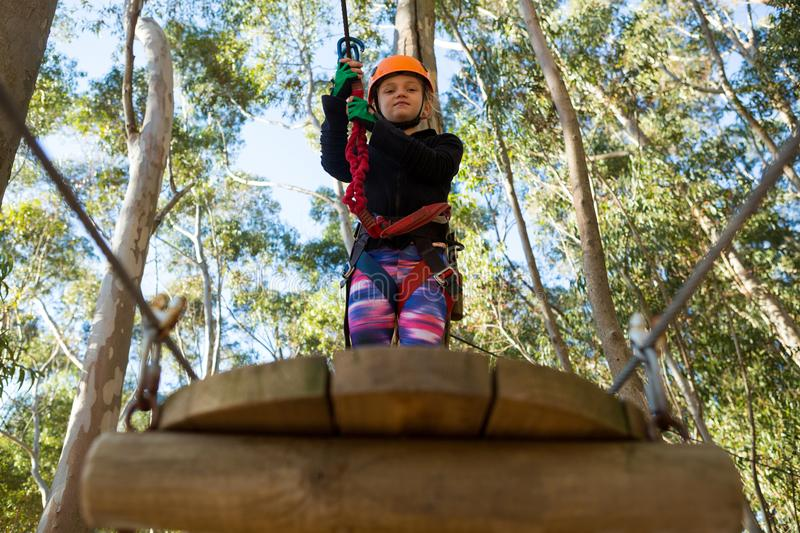 Little girl wearing helmet holding rope and standing on wooden platform stock photography