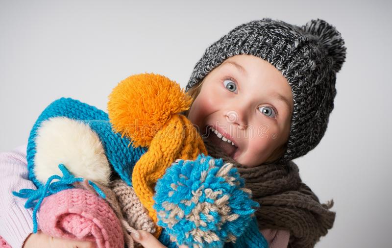 Little girl wearing knitted hat, scarf and sweater, holding a pile of hats, royalty free stock image