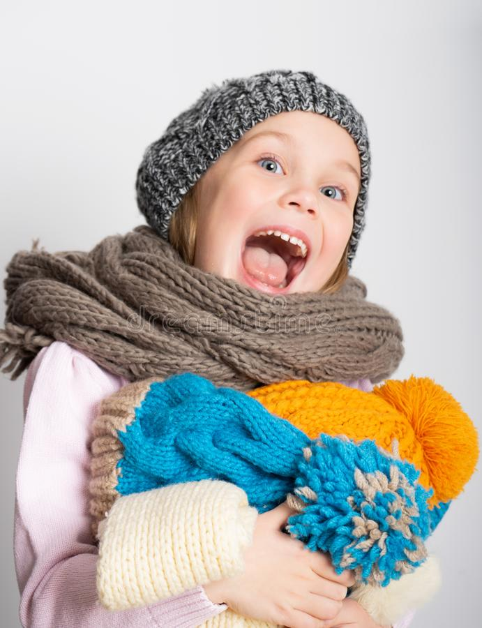 Little girl wearing knitted hat, scarf and sweater, holding a pile of hats, royalty free stock images