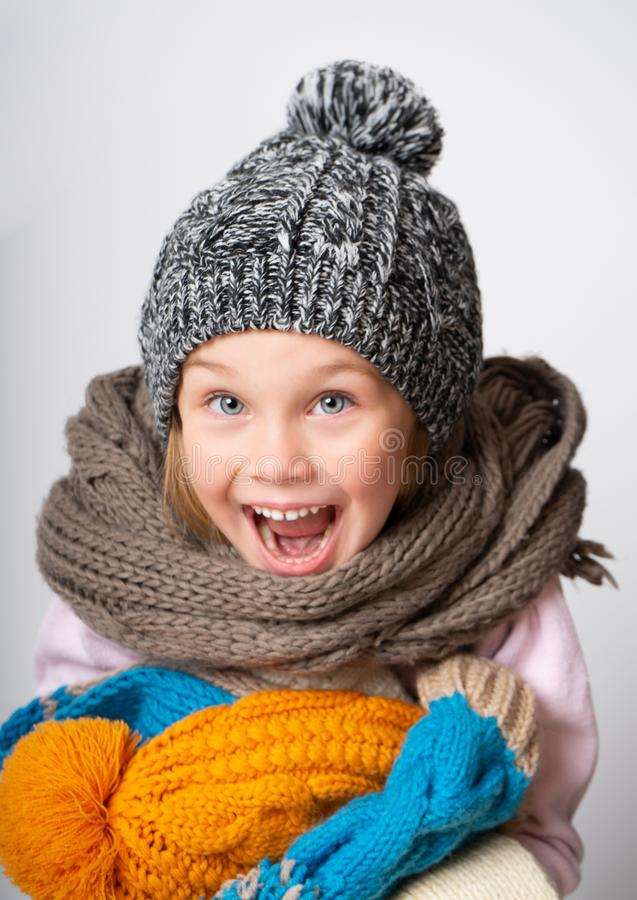 Little girl wearing knitted hat, scarf and sweater, holding a pile of hats, stock image