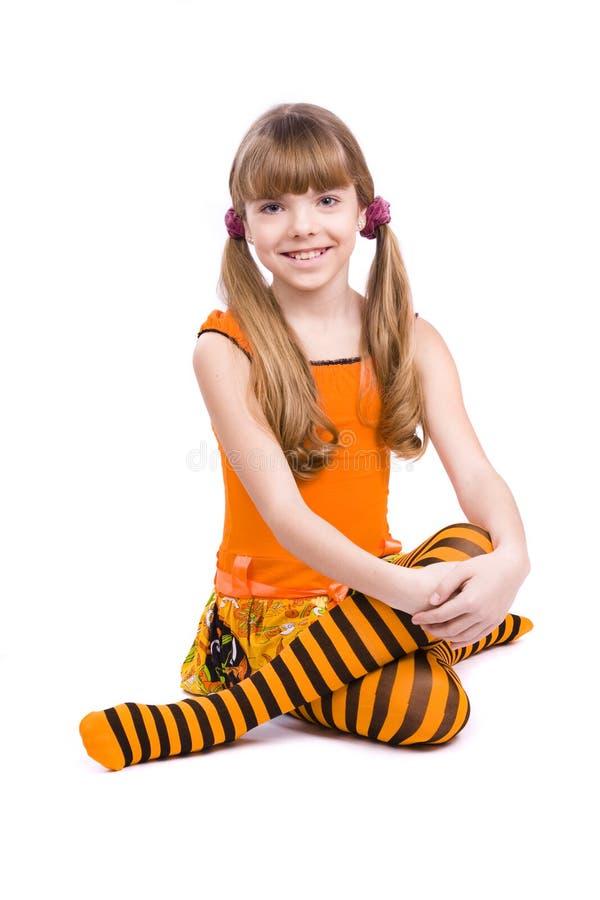 Little girl wearing orange dress is sitting