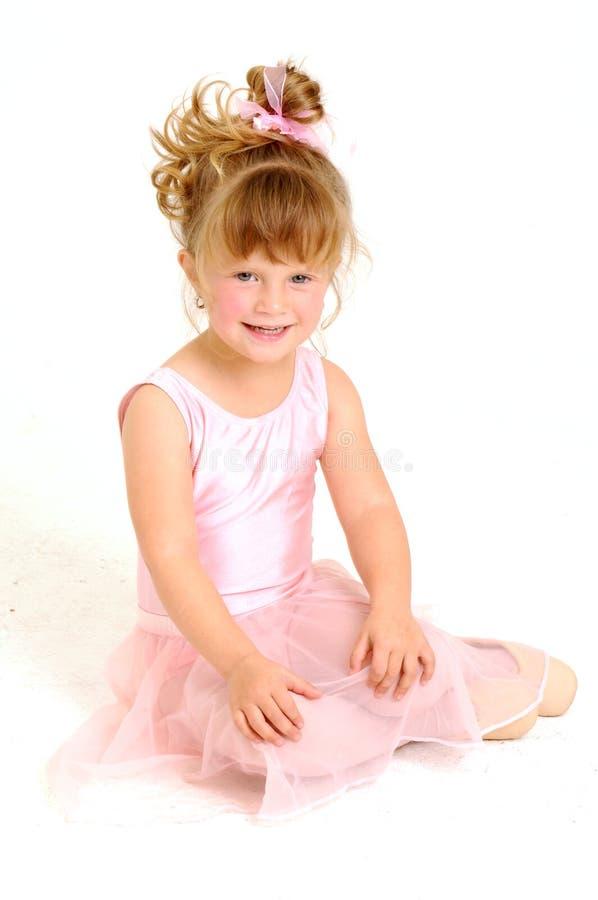 Little girl wearing pink ballet dress sitting stock photos
