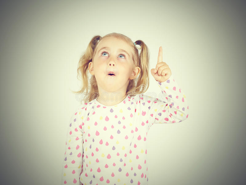 Little girl wearing pointing by forefinger to somewhere up. Isolated royalty free stock images