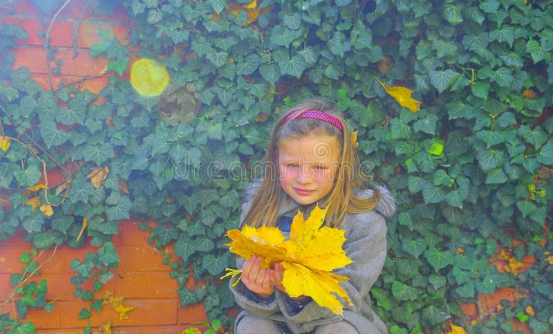 Little girl wearing retro coat and crouching in front of brick wall in autumn. Ivy wall in autumn. Autumn concept. Lens flare royalty free stock photo