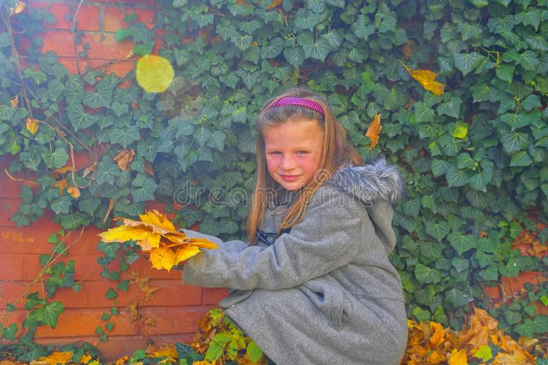 Little girl wearing retro coat and crouching in front of brick wall in autumn. Ivy wall in autumn. Autumn concept. Lens flare royalty free stock images