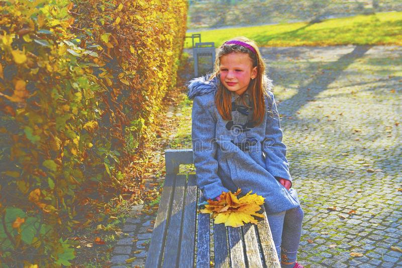 Little girl wearing retro coat and sitting on bench in park in autumn. Small girl is holding colorful autumn leaves. Autumn concep stock photo