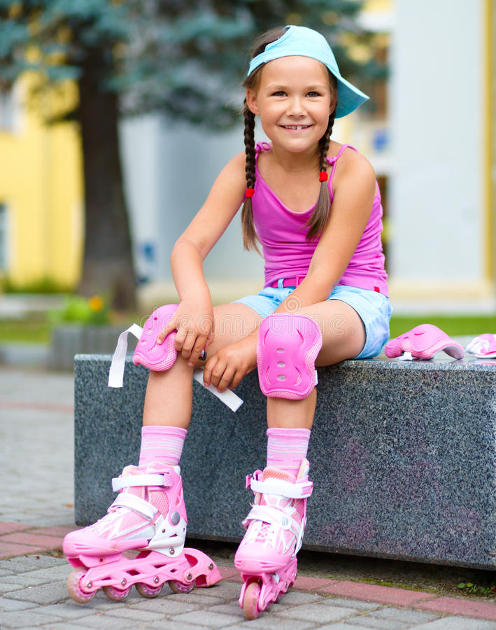 Little girl is wearing roller-blades. In city park royalty free stock photos