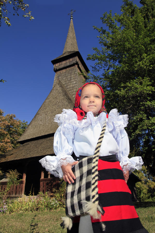 Little girl wearing Romanian traditional clothing and traditional wood church on a background. Romania stock image
