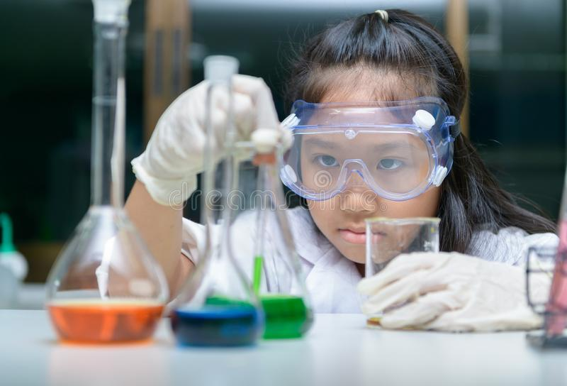 Little girl wearing safty goggle making experiment royalty free stock image