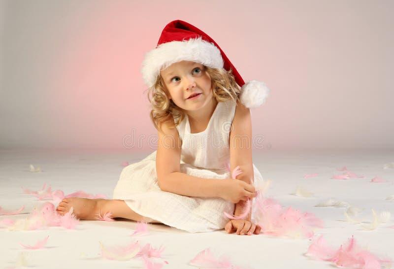 Little girl wearing Santa hat royalty free stock photography