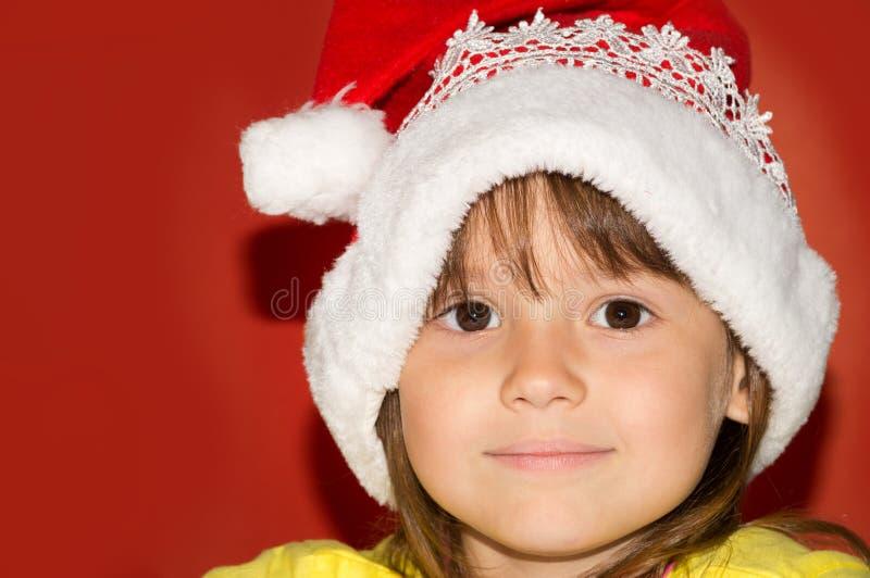 Little girl wearing santa hat. Smiling royalty free stock photo