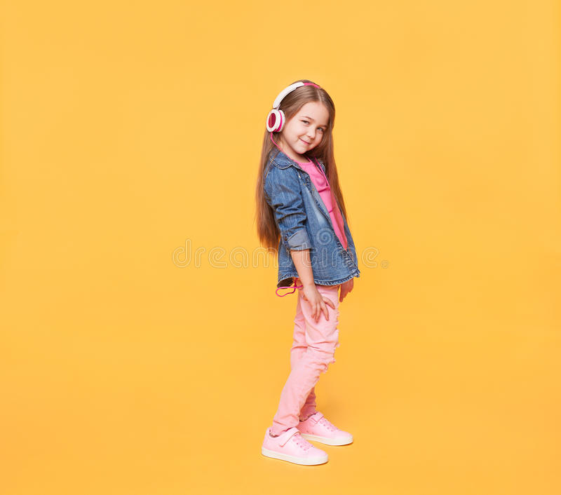 Little girl wearing stylish clothes on yellow colorful background. Modern little girl wearing stylish clothes on yellow colorful background. Full body portrait stock photo