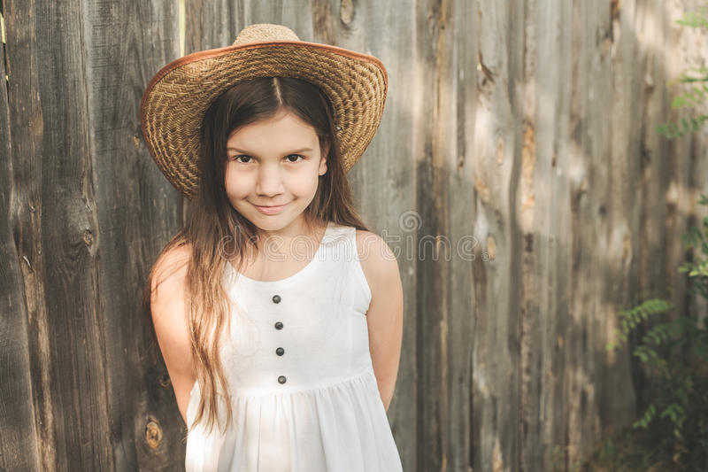 Little girl wearing white rustic dress and straw hat stays on the wooden fence background. In the sunny summer day stock photo