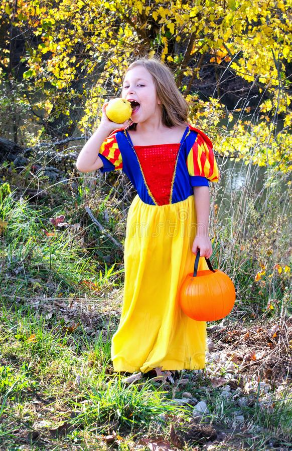Girl in a princess costume with a juicy apple royalty free stock photo