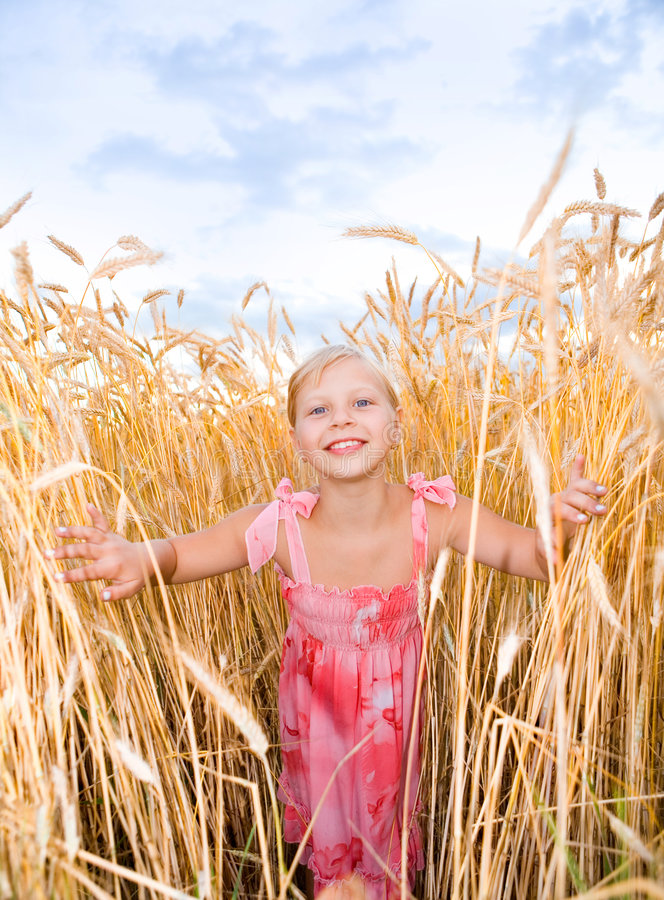Little girl in a wheat field. Against backdrop of cloudy skies royalty free stock images