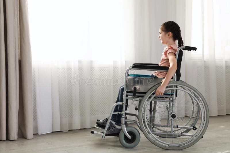 Little girl in wheelchair near window indoors stock images