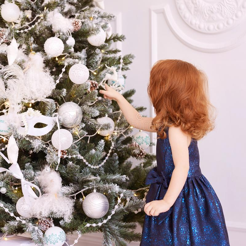 Little girl. White background. Blue dress. Christmas decorations royalty free stock photos
