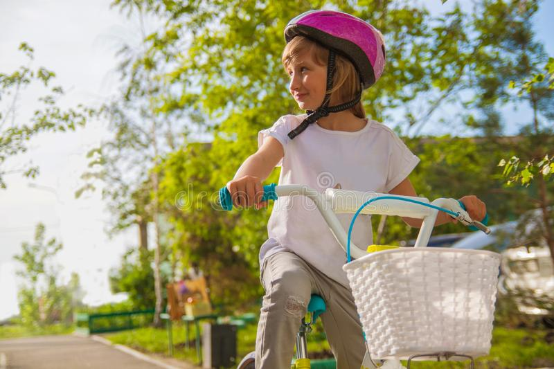 The kid with blonde hair in a helmet riding a bike in the park. Beautiful baby. royalty free stock photography