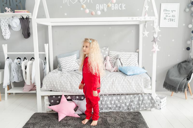 Little girl with white curly hair in red pajamas laughing at children`s room.  stock photography