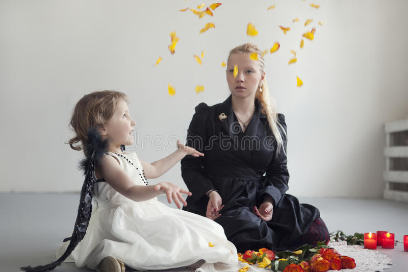 Little girl in white dress with artificial black wings sits with mom on the floor. Little girl in white dress with an artificial black wings sits with mom on the royalty free stock photography