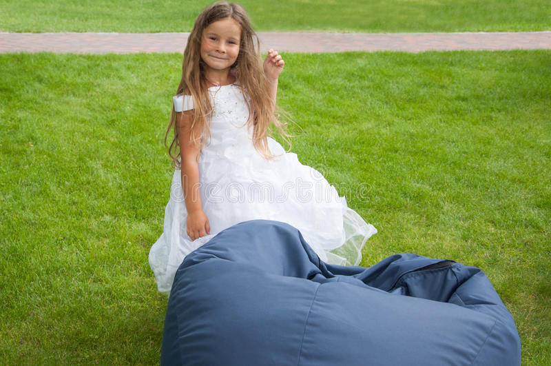 Little girl in white dress, bride, bean-bag, happy. A little girl in a white dress, happy, near bean bag stock photography