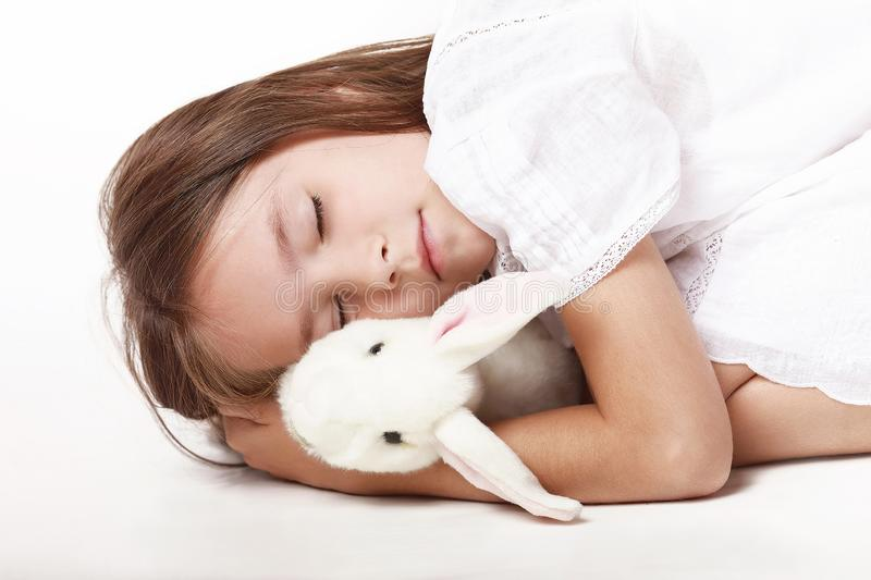A little girl in a white dress, sleeps a cripple with a favorite toy against a white background. Dream. Happy childhood stock image