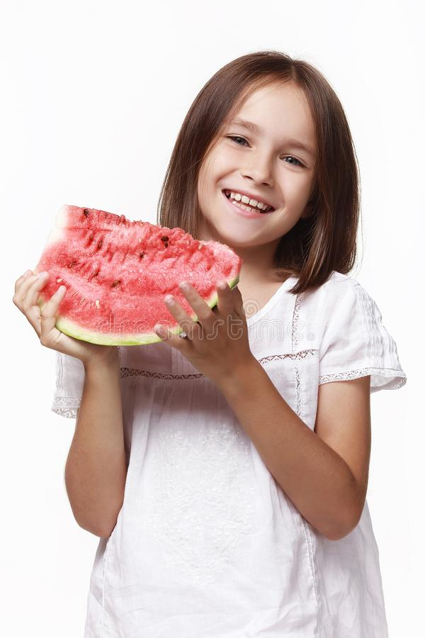 A little girl in a white dress in a studio on a white background with a piece of watermelon,. Laughs. Happy childhood, pampering. t, proper nutrition stock photo