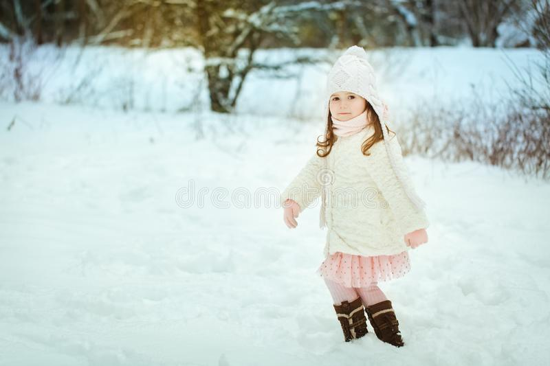 Little girl in a white fur coat in the winter forest royalty free stock photos