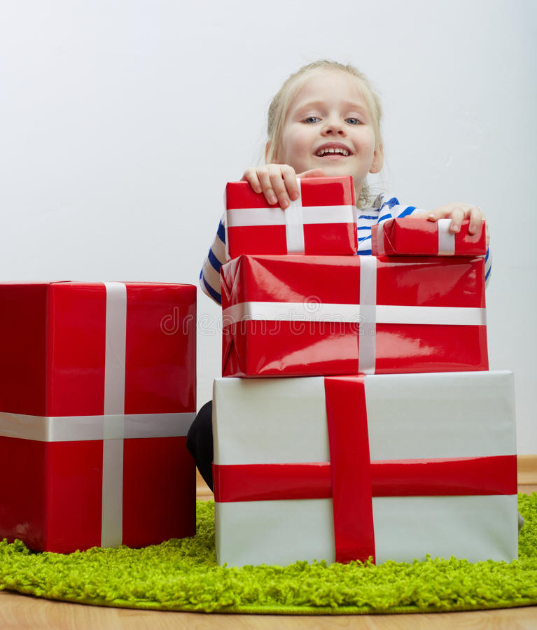 Little girl with white hair and many gifts stock photo