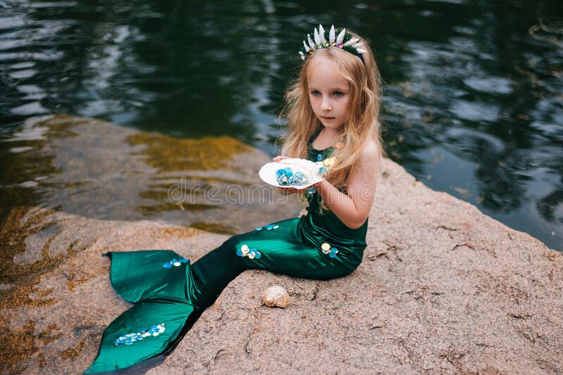 A little girl with white hair with a mermaid tail and shells is sitting on the shore. A little mermaid sits on a large stone by royalty free stock photos