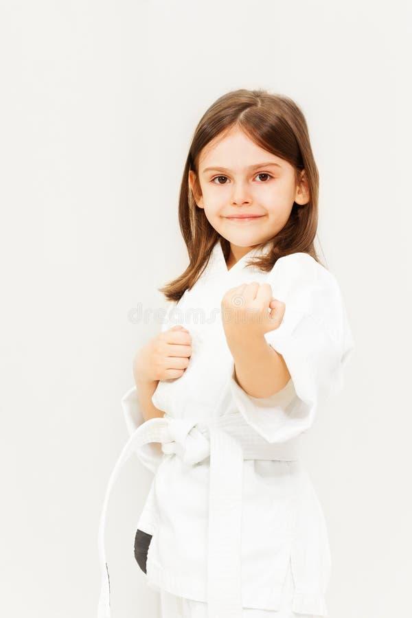 Little girl in white kimono training karate stock photos