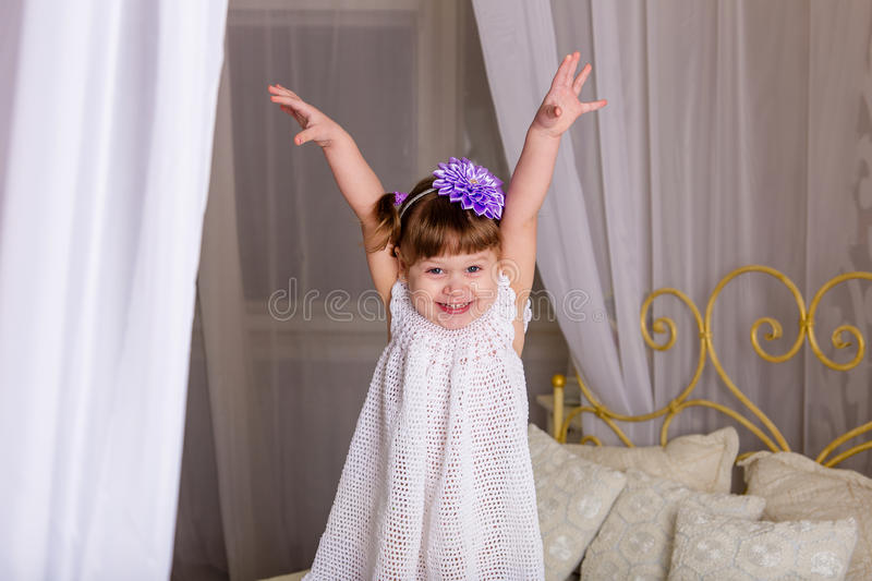 A little girl in a white knitted dress pampered on a bed. Before going to bed royalty free stock images