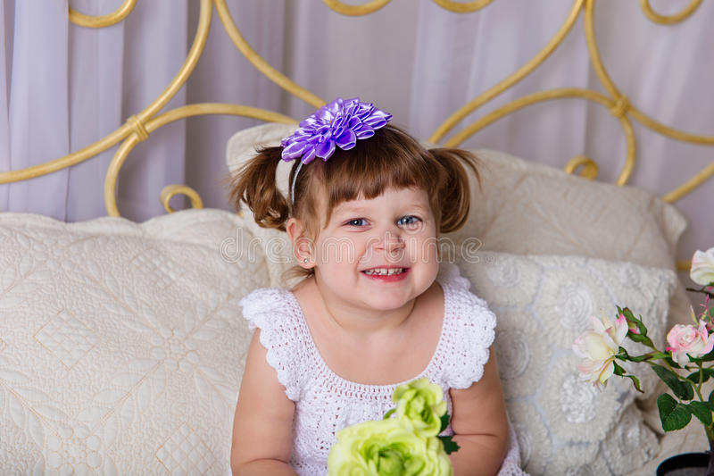A little girl in a white knitted dress pampered on a bed. Before going to bed stock photos