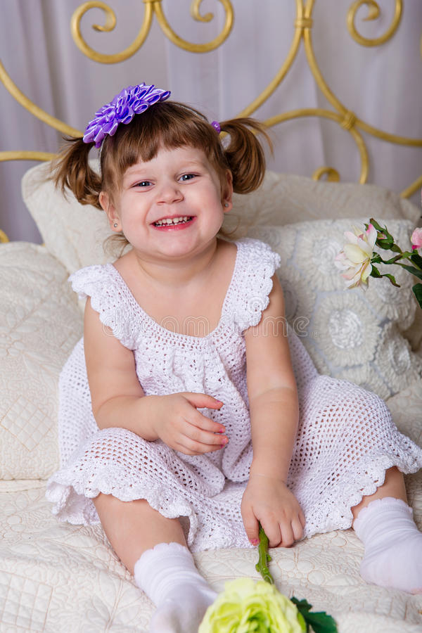 A little girl in a white knitted dress pampered on a bed. Before going to bed stock photo