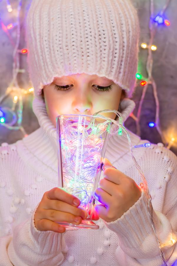 Little girl in a white knitted sweater and hat drinks from a glass multi-colored lights of a Christmas garland. Creative christmas royalty free stock photos