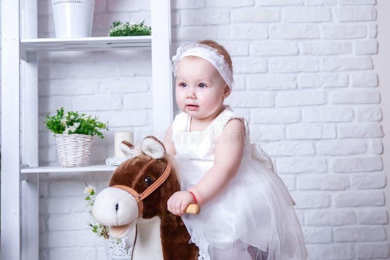 Little girl in white lush dress on horseback royalty free stock image