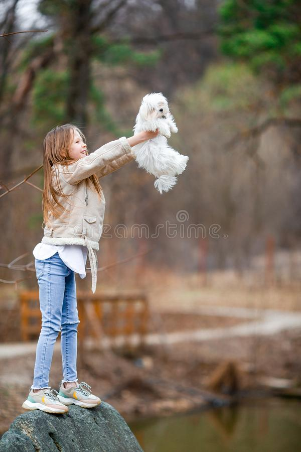 Little girl with a white puppy. A puppy in the hands of a girl. Little happy girl with white puppy outdoors. She is very happy to play with her pet royalty free stock image