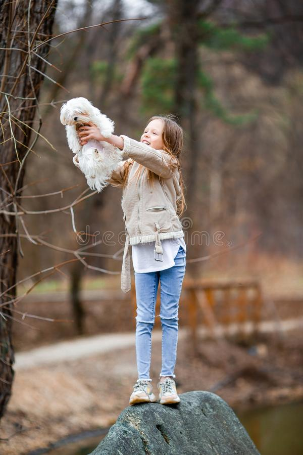 Little girl with a white puppy. A puppy in the hands of a girl. Little happy girl with white puppy outdoors. She is very happy to play with her pet stock photography