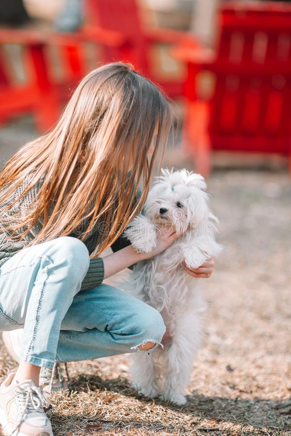 Little girl with a white puppy. A puppy in the hands of a girl. Little happy girl with white puppy outdoors. She is very happy to play with her pet royalty free stock images