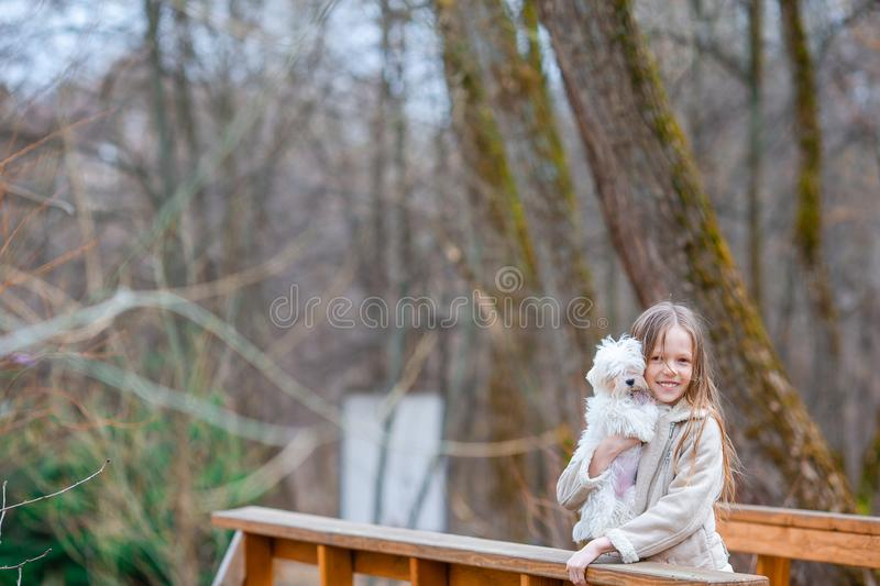 Little girl with a white puppy. A puppy in the hands of a girl. Little happy girl with white puppy outdoors. She is very happy to play with her pet royalty free stock photo