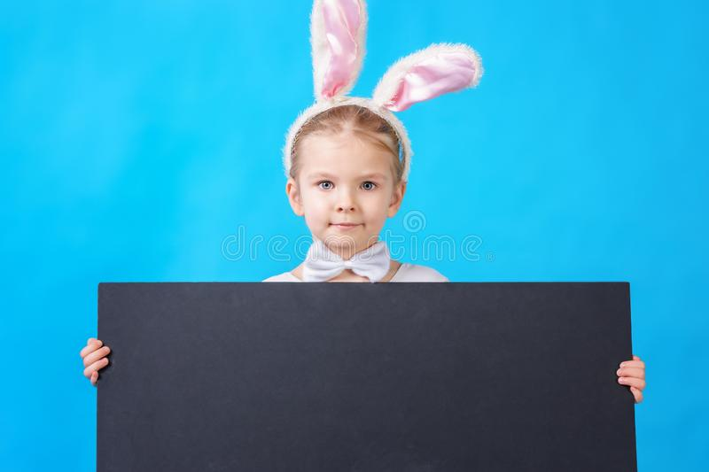 Little girl in a white rabbit costume on a blue background. Copy space on black cardboard. Beautiful photo with space royalty free stock photo
