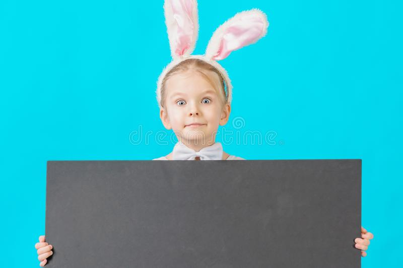 Little girl in a white rabbit costume. The child is holding a black sheet with space for text. Bright layout. Little girl in a white rabbit costume. The child royalty free stock photos